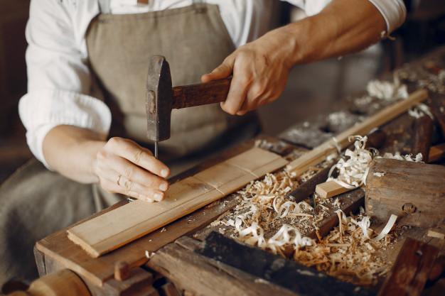 Άνδρας με σφυρί επεξεργάζεται ξύλο
