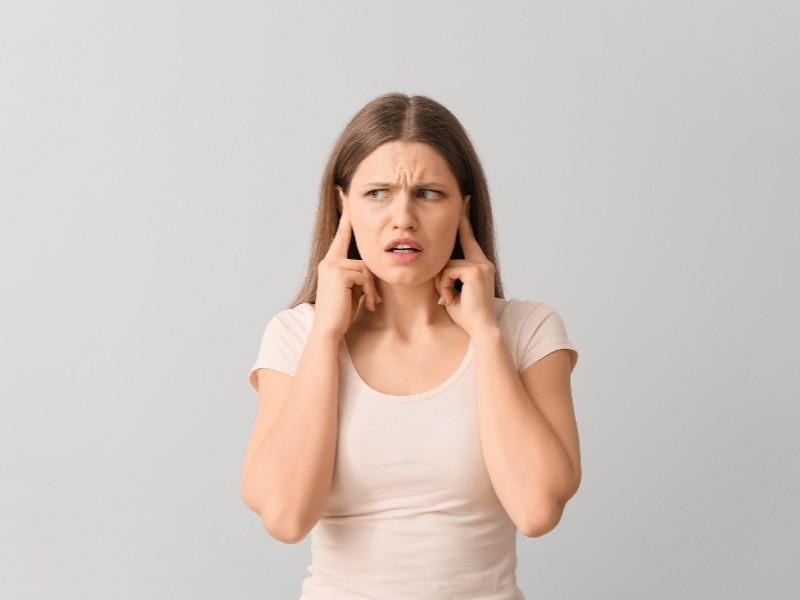 Κοπέλα με λευκή μπλούζα κλείνει τα αυτιά της