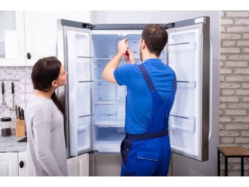 Γυναίκα Δίπλα από τεχνικό ψυγείου που επισκευάζει ψυγείο