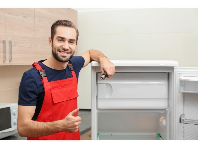 Τεχνικός Ψυγείου Χαμογελάει Κρατώντας Εργαλείο Μπροστά Από Ψυγείο